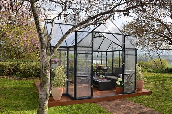 orangery style greenhouse in a garden setting