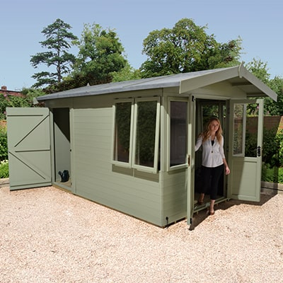 a green summerhouse with a lady standing in the open door way and a rear shed area with door open