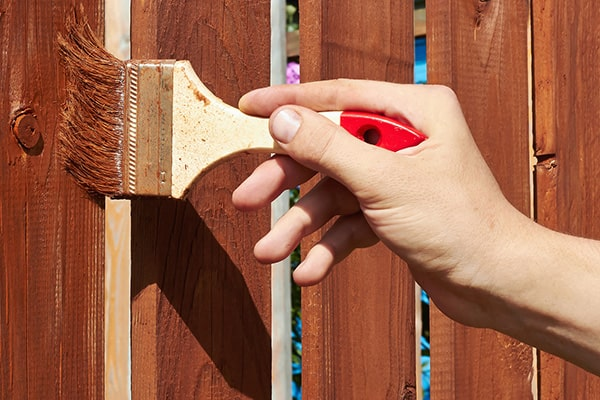 someone using a brush to apply paint or stain to a fence