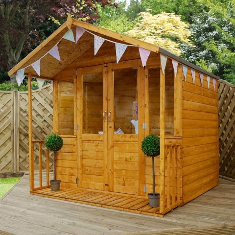 The 7x7 Windsor Traditional Wooden Summer House, situated on garden decking, with 2 plants on the veranda and triangular flags pinned to the eaves.